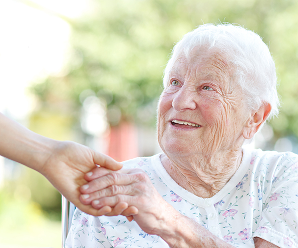Senior woman smiling and holding hands with caretaker