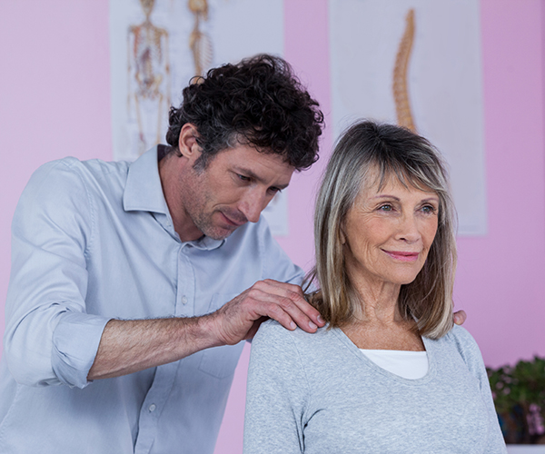 Male Physiotherapist giving shoulder massage to woman patient