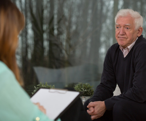 grey haired man sitting talking to a woman