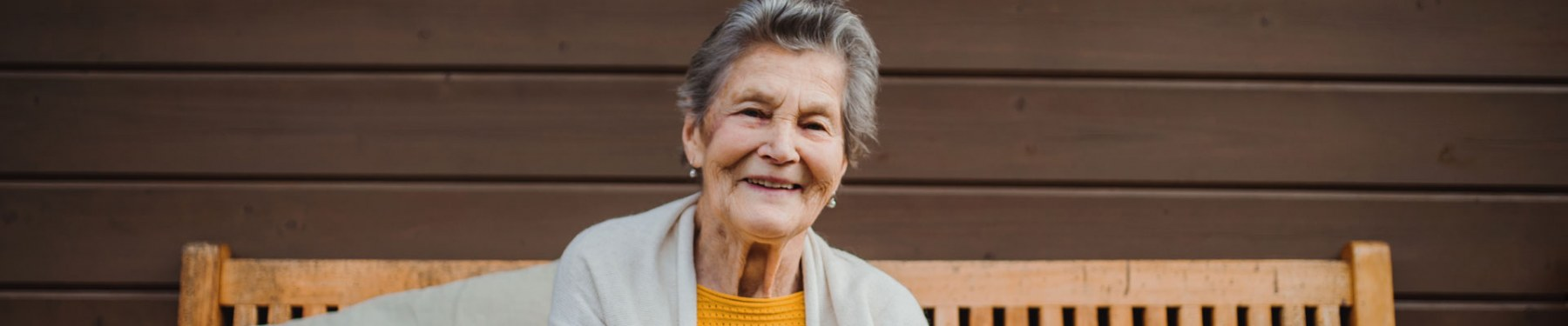 smiling older woman sitting on a wooden bench