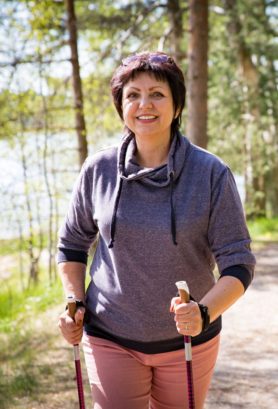 woman walking on wooded trail using hiking sticks