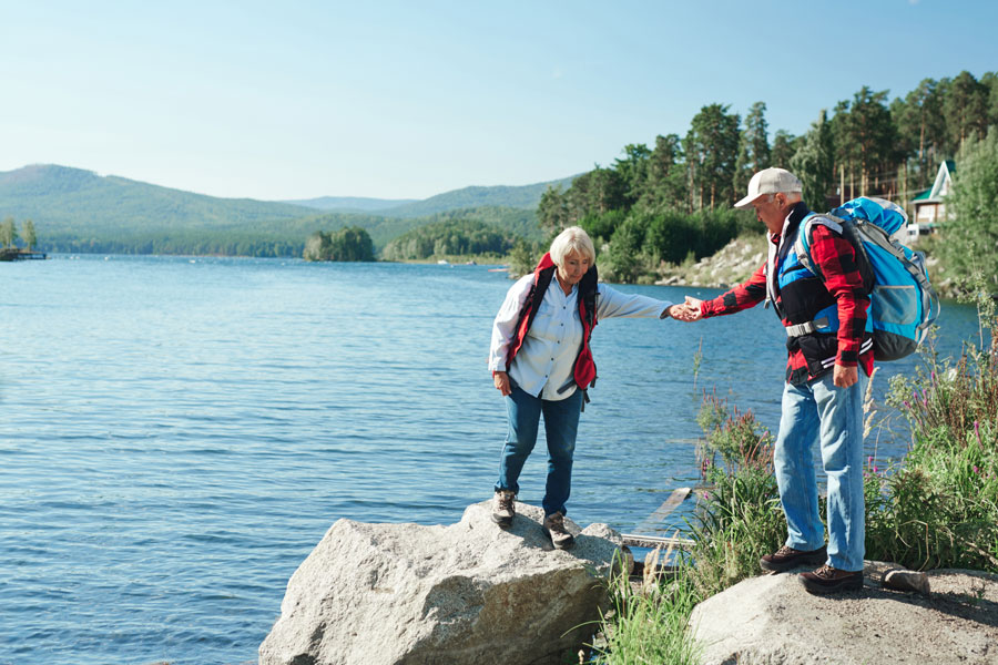 older man helping an older woman across the rocks while hiking